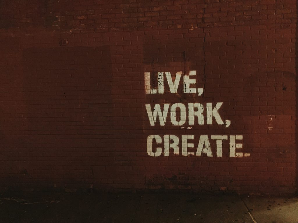 motivational message on a wall, live, work create